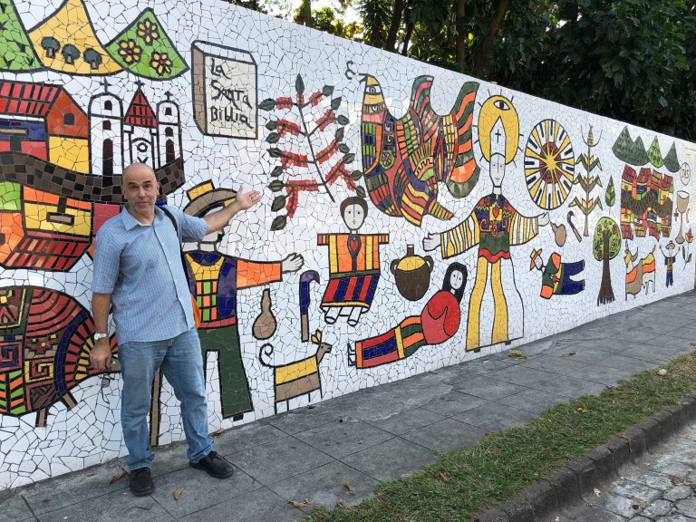 Peter Altman stops at a mural to martyred St. Oscar Romero, near the chapel where the archbishop was slain in 1980 in San Salvador.